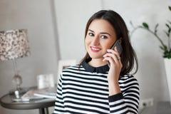 Η μοντέρνη νέα γυναίκα με όμορφο αποτελεί την ομιλία στο τηλεφωνικό amd χαμόγελο κυττάρων της στη κάμερα Στοκ εικόνα με δικαίωμα ελεύθερης χρήσης