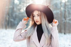 Η μοντέρνη όμορφη γυναίκα στο κομψό καπέλο και το παλτό που περπατά κερδίζουν Στοκ Φωτογραφία