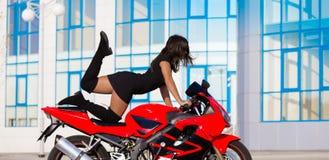 Η μοτοσικλέτα, γυναίκα, μοναδική θέτει Στοκ Φωτογραφίες