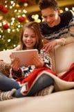 Η μουσική ακούσματος κοριτσιών και απολαμβάνει με τον αδελφό για τη Παραμονή Χριστουγέννων Στοκ φωτογραφία με δικαίωμα ελεύθερης χρήσης