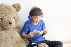Η μουσική ακούσματος μικρών παιδιών και διαβασμένος ένα βιβλίο για χαλαρώνει στοκ φωτογραφία με δικαίωμα ελεύθερης χρήσης
