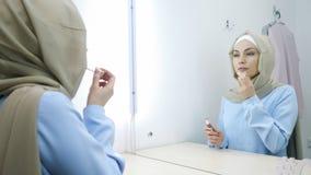 Η μουσουλμανική γυναίκα στο hijab ισχύει lipgloss στα χείλια της που στέκονται μπροστά από τον καθρέφτη απόθεμα βίντεο