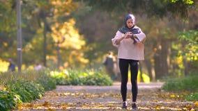 Η μουσουλμανική γυναίκα στο hijab πηγαίνει στο φθινοπωρινό πάρκο, σταματά για να ελέγχει το ρολόι και συνεχίζει απόθεμα βίντεο