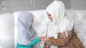 Η μουσουλμανική οικογένεια mom και η κόρη στα hijabs κάθονται στον καναπέ και mom φιλά τα χέρια του κοριτσιού απόθεμα βίντεο