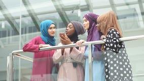 Η μουσουλμανική multiethnic ομάδα κοριτσιών εξετάζει το έξυπνο τηλέφωνο υπό εξέταση της αφρικανικής γυναίκας απόθεμα βίντεο