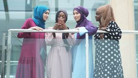 Η μουσουλμανική multiethnic ομάδα κοριτσιών εξετάζει το έξυπνο τηλέφωνο υπό εξέταση της αφρικανικής γυναίκας φιλμ μικρού μήκους