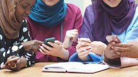 Η μουσουλμανική multiethnic ομάδα κοριτσιών που εξετάζουν τα smartphones διαθέσιμα, κλείνει επάνω φιλμ μικρού μήκους