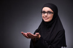 Η μουσουλμανική γυναίκα στο μαύρο φόρεμα στο σκοτεινό κλίμα Στοκ Εικόνες