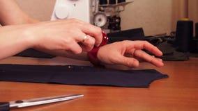 Η μοδίστρα αποκόπτει το ύφασμα Το κορίτσι κόβει το ύφασμα με το ψαλίδι Καρφίτσες πληγμάτων στο ύφασμα φιλμ μικρού μήκους
