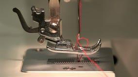 Η μοδίστρα κάτω από τη βελόνα μέσω του πιάτου βελόνων και κάνει έναν βρόχο για το ράψιμο σε μια ράβοντας μηχανή απόθεμα βίντεο