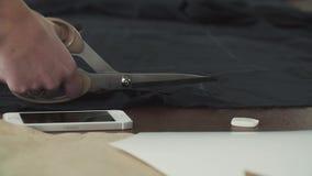 Η μοδίστρα κόβει το μαύρο ύφασμα στον πίνακα φιλμ μικρού μήκους