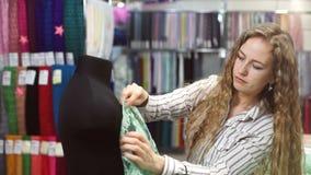 Η μοδίστρα σχεδιάζει το ύφασμα στο μανεκέν σε αναζήτηση των ιδεών για το φόρεμα απόθεμα βίντεο