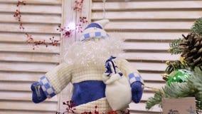 Η μπλε-και-άσπρη κούκλα Άγιου Βασίλη με την παχιά γενειάδα και το καπέλο, κάθεται στην εστία απόθεμα βίντεο