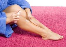 η μπλε κρέμα μπουρνουζιών έντυσε το πόδι της που τρίβει τις νεολαίες γυναικών στοκ εικόνες