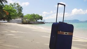 Η μπλε μικρή βαλίτσα στέκεται στην ακτή μιας όμορφης θάλασσας, μιας αναμενόμενης για καιρό έννοιας ελεύθερου χρόνου, ενός ταξιδιο φιλμ μικρού μήκους