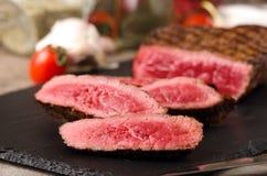 Η μπριζόλα βόειου κρέατος ασφαλίστρου τεμάχισε το μαύρο πιάτο στοκ φωτογραφία