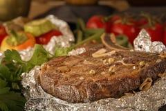 Η μπριζόλα κρέατος έψησε στο φύλλο αλουμινίου και έψησε τα λαχανικά σε έναν ξύλινο πίνακα με τις φρέσκες ντομάτες και τα πράσινα στοκ εικόνες