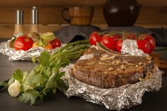 Η μπριζόλα κρέατος έψησε στο φύλλο αλουμινίου και έψησε τα λαχανικά σε έναν ξύλινο πίνακα με τις φρέσκες ντομάτες και τα πράσινα στοκ φωτογραφίες με δικαίωμα ελεύθερης χρήσης