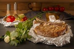 Η μπριζόλα κρέατος έψησε στο φύλλο αλουμινίου και έψησε τα λαχανικά σε έναν ξύλινο πίνακα με τις φρέσκες ντομάτες και τα πράσινα στοκ φωτογραφία με δικαίωμα ελεύθερης χρήσης