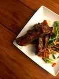 Η μπριζόλα πλευρών χοιρινού κρέατος με τη juicy σάλτσα σχαρών και η σαλάτα βάζουν στο ξύλινο επιτραπέζιο υπόβαθρο στοκ φωτογραφίες