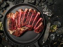 Η μπριζόλα κόβεται και βρίσκεται σε ένα τηγανίζοντας τηγάνι Στοκ Εικόνες