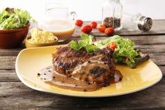 Η μπριζόλα που τίθεται με τη μαύρη σάλτσα πιπεριών και την πατάτα Στοκ εικόνες με δικαίωμα ελεύθερης χρήσης