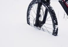 Η μπροστινή ρόδα της παραμονής ποδηλάτων βουνών στο χιόνι σκονών Χαμένη πορεία Στοκ Εικόνες