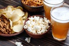 Η μπύρα τσιμπά στον ξύλινο πίνακα - καρύδια, τσιπ και popcorn στα κύπελλα έτοιμα για την κατανάλωση Στοκ Εικόνες
