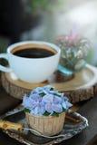 Η μπλε κρέμα σχεδίου cupcake όπως το μπλε λουλούδι Hydrangea εξυπηρέτησε με τον καυτό μαύρο καφέ στο ξύλινο επιτραπέζιο υπόβαθρο Στοκ εικόνα με δικαίωμα ελεύθερης χρήσης