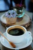 Η μπλε κρέμα σχεδίου cupcake όπως το μπλε λουλούδι Hydrangea εξυπηρέτησε με τον καυτό μαύρο καφέ στο ξύλινο επιτραπέζιο υπόβαθρο Στοκ Εικόνα