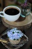 Η μπλε κρέμα σχεδίου cupcake όπως το μπλε λουλούδι Hydrangea εξυπηρέτησε με τον καυτό μαύρο καφέ στο ξύλινο επιτραπέζιο υπόβαθρο Στοκ φωτογραφία με δικαίωμα ελεύθερης χρήσης