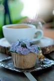 Η μπλε κρέμα σχεδίου cupcake όπως το μπλε λουλούδι Hydrangea εξυπηρέτησε με τον καυτό μαύρο καφέ στο ξύλινο επιτραπέζιο υπόβαθρο Στοκ εικόνες με δικαίωμα ελεύθερης χρήσης