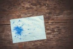 Η μπλε Λευκή Βίβλος φύλλων λεκέδων του μελανιού για μια ξύλινη επιφάνεια Στοκ Φωτογραφία