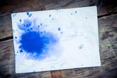 Η μπλε Λευκή Βίβλος φύλλων λεκέδων του μελανιού για μια ξύλινη επιφάνεια Στοκ εικόνα με δικαίωμα ελεύθερης χρήσης