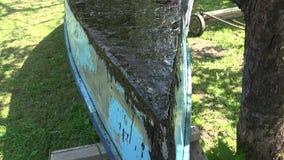 Η μπλε ξύλινη βάρκα και ο νεαρός άνδρας βάζουν την καυτή πίσσα με το πρωταρχικό εργαλείο καυστήρων αερίου 4K απόθεμα βίντεο