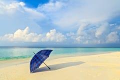 Η μπλε ομπρέλα είναι σε μια παραλία στοκ εικόνες με δικαίωμα ελεύθερης χρήσης