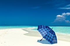Η μπλε ομπρέλα είναι σε μια παραλία στοκ φωτογραφίες με δικαίωμα ελεύθερης χρήσης