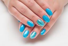 Η μπλε στιλβωτική ουσία καρφιών με ακτινοβολεί στο δάχτυλο δαχτυλιδιών Στοκ Φωτογραφία