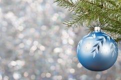 Η μπλε σφαίρα Χριστουγέννων σε έναν κλάδο χριστουγεννιάτικων δέντρων πέρα από το θολωμένο λαμπρό υπόβαθρο, κλείνει επάνω Στοκ Φωτογραφία
