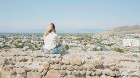 Η μυστήρια κυρία με τη φωτεινή πετώντας βαμμένη τρίχα κάθεται στην άκρη της βάρκας πετρών στο βράχο και θαυμάζει τη γραφική άποψη απόθεμα βίντεο