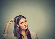 Η μωλωπισμένη σκεπτόμενη γυναίκα που συγχέεται γρατσούνισμα του κεφαλιού της επιδιώκει μια λύση Στοκ Φωτογραφία