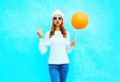 Η μόδα που το δροσερό κορίτσι στέλνει ένα φιλί αέρα κρατά το μπαλόνι στο άσπρο καπέλο Στοκ εικόνες με δικαίωμα ελεύθερης χρήσης