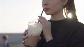 Η μόνη γυναίκα πίνει τον καφέ, κρατώντας το φλυτζάνι στα χέρια υπαίθρια το θερινό βράδυ απόθεμα βίντεο