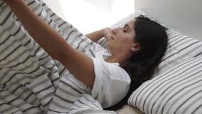 Η μόνη γυναίκα brunette ξυπνά στην κρεβατοκάμαρα το πρωί, καθμένος στην άκρη του κρεβατιού φιλμ μικρού μήκους
