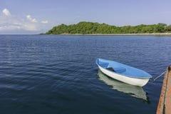 Η μόνη μικρή μπλε βάρκα δεσμεύει στο μεγάλο σκάφος Στοκ Φωτογραφία