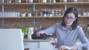 Η μόνη νοικοκυρά κοριτσιών χύνει το κρασί στην κουζίνα στοκ φωτογραφίες