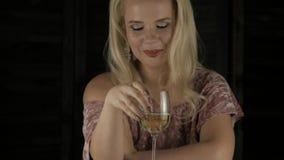 Η μόνη πολυτελής ξανθή γυναίκα πίνει τη σαμπάνια μόνο στο σκοτάδι σε ένα κόμμα κίνηση αργή απόθεμα βίντεο