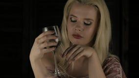 Η μόνη πολυτελής ξανθή γυναίκα πίνει τη σαμπάνια μόνο στο σκοτάδι σε ένα κόμμα 4K απόθεμα βίντεο