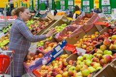 Η Μόσχα, Ρωσία, μπορεί το 2018: Μια γυναίκα επιλέγει τα μήλα σε ένα supermarke στοκ φωτογραφία