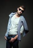 Η μόδα στούντιο πυροβόλησε: όμορφος νεαρός άνδρας που φορά τα τζιν, το πουκάμισο και τα γυαλιά ηλίου Στοκ Φωτογραφία